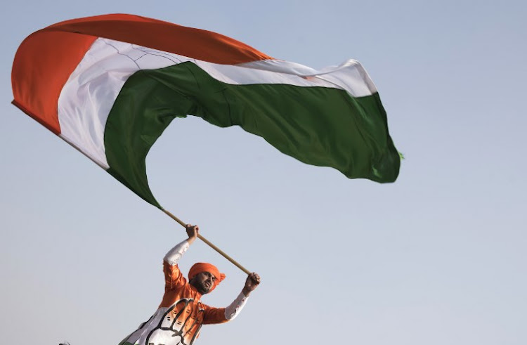 A supporter waves an Indian flag during a political rally.
