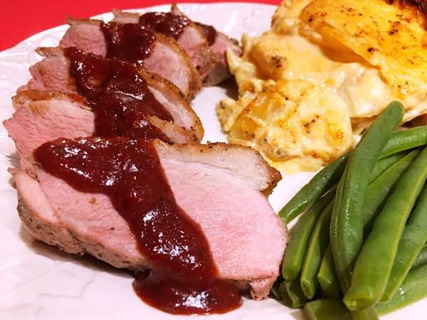 A Few Slices Of Duck Breast On A Plate Along With Green Beans And Potatoes.
