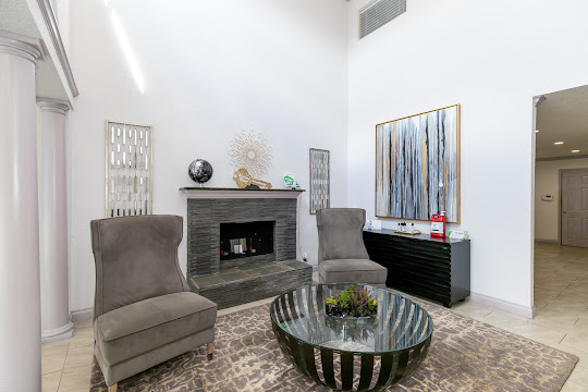 Clubhouse seating area with comfortable chairs, fireplace, and modern wall decorations