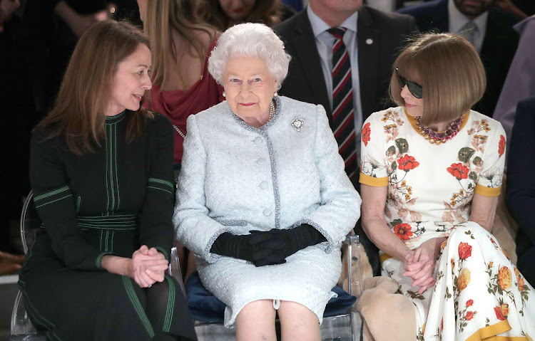 Queen Elizabeth II sits next to Anna Wintour (R) and Caroline Rush (L) at London Fashion Week