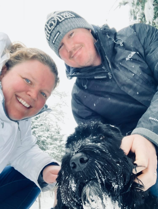 couple walk dog snow
