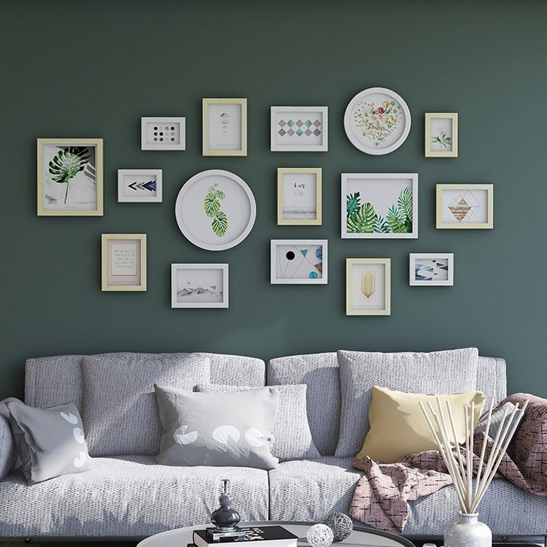 16 gallery wall frames of various shapes and sizes above a gray couch on a green wall