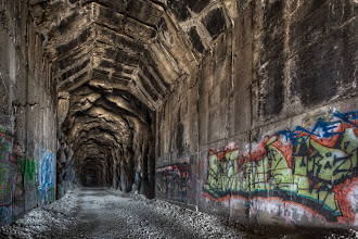 Photo: Burrowed  This was the first set of bracketed photos that I took when +Karen Huttonand +Joe Dolisterbrought +Nicole S. Youngand me to this beautifully ornate abandoned train tunnel. My initial instinct was to plot down right in the center of the tunnel and take a head-on shot. When I looked through the Live View, though, the whole image immediately felt flat. There wasn't anything really drawing me through the frame and for a scene as texture-rich as this one, that is a critical goal to have.  So, by shifting the camera over more to the left (but not quite hugging the wall), I was able to introduce some leading lines to help draw the eyes through the frame. This little visual trick was also supplemented with specific stylization techniques to brighten key areas and darken others, further helping out my goal.  I used my Canon 5D Mark III and Canon 17mm T/S lens to grab the frames, tone-mapped using Photomatix Pro and stylized using Color Efex Pro 4, part of the Nik Collection by Google.