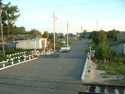 Ein typischer Bahnübergang, der den Stellenwert einer Verkehrsader, wie der Transsib verdeutlicht: Auch der gottverlassenste Bahnübergang ist beschrankt und meist mit einer Straßenbarriere versehen.