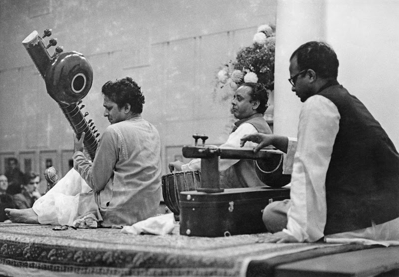 Photo: Indian musician and composer Ravi Shankar (left) playing a sitar in a concert with tabla playerAlla Rakha (1919 - 2000, centre) and tanpura player Prodyot Sen, 15th October 1958. (Photo by Erich Auerbach/Hulton Archive/Getty Images)