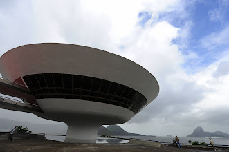 Photo: People at the Contemporary Art Museum, designed by Brazilian architect Oscar Niemeyer, in Niteroi, a city 25 km from Rio de Janiero just across Guanabara Bay, watch the storm over Rio on April 9, 2010. The unusual roughness seen these days in the bay is according to experts, caused by the same climate phenomenon that originated the heaviest rains in half a century that since Monday unleashed the floods and mudslides which killed an estimate of 380 people in the state of Rio de Janeiro. Rescuers resumed on Friday a grim search through a wall of mud with hopes fading of finding survivors as more than 380 people are now feared to have died in Brazil's worst rains in decades.  AFP PHOTO/VANDERLEI ALMEIDA (Photo credit should read VANDERLEI ALMEIDA/AFP/Getty Images)