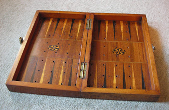 "Photo: CH110; interior of the box showing the attractive backgammon board.  Note: (i) the holes for the pegged chess pieces come all the way through but do not align with the backgammon points. A similar board (see: http://www.crumiller.com/chess/chess_pages/staunton/JaquesStauntonShippingSet.htm) also has the holes 'out of' allignment, as advised by Jon.  Odd - it does spoil the look (not to mention the efficacy) considerably. This seems to be the case with other ""ships' boards""  I have heard of. However, I have recently seen one by a well-known maker where the alignment is perfect: is this just greater care taken or are the boards, such as that above, simply 'after-conversions' or 'fakes'? See CH305, as I have now acquired this H.Witty board.  Note: (ii) the catches for the fastener (see next image) protrude downwards (one-side can be moved up, but not the other) which means the board does not sit flat on a table or other large surface. Is this a later addition?"