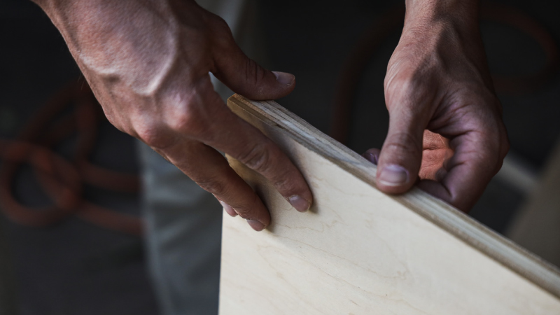A person handling a plywood plank