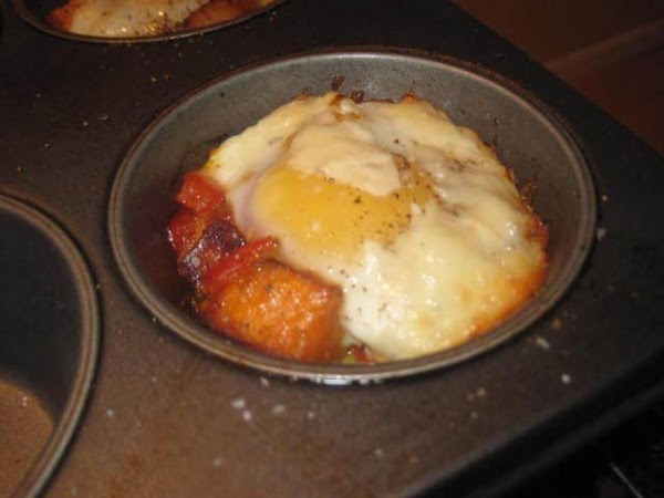 Crack one egg over each hash filled muffin tin, sprinkle with kosher salt and...