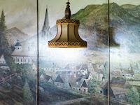 muurschildering van een dorpsgezicht met een hangende lamp ervoor