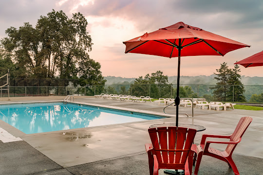 The Flats at Fox Hill apartment swimming pool with view of wooded area at dusk