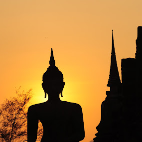 Silhouetted Buddha statue in Thailand. by Jesadaphorn Chaiinkaew - Buildings & Architecture Statues & Monuments ( buddha; buddhism; statue; silhouette; chedi; sukhothai; thailand; worship; holy; asia; art; culture; traditional; evening; sky; sunset; orange; temple. )