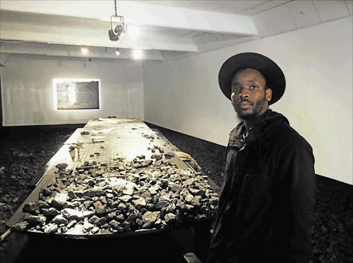 Thought-provoking: Young Artist for Visual Art Mohau Modisakeng at his festival exhibition, Lefa la Ntate, showing the black male in relation to the economy and society, past, present and future Picture: GILLIAN McAINSH