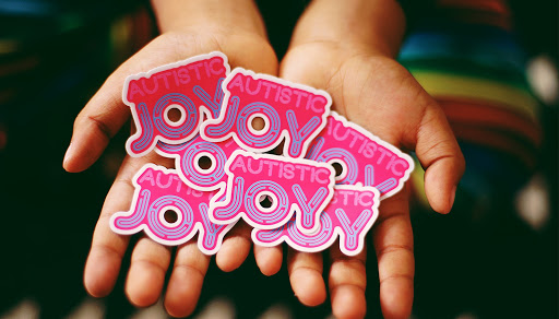 "Custom stickers in pink and lavender that read ""Austistic Joy"""