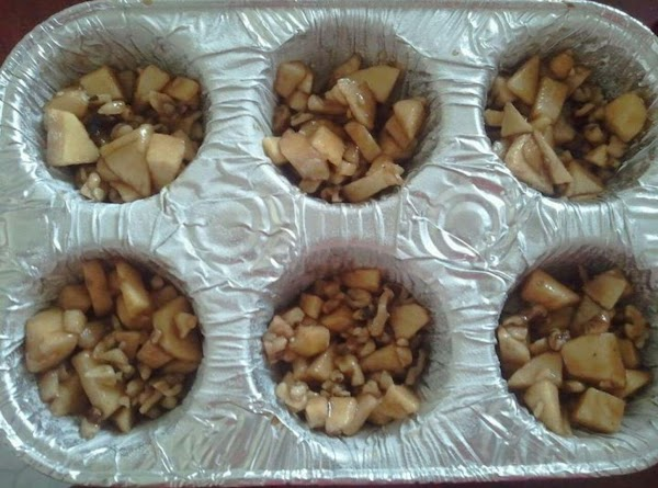 Divide the apple mixture evenly into the muffin tin. Put 12 cinnamon buns, cinnamon...