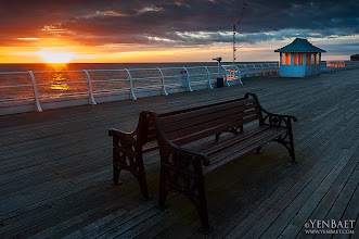 Photo: Empty Benches on the Pier at Sunset - Cromer, U.K.  An inviting scene at the pier and one that came in handy at that time. I found the other half of the pier with the Pavilion Theatre under construction when I got there, and with that irresistible sky, I had to be more creative and luckily found these lonely benches as great alternate subjects. The orange glow bouncing off from the hut on the right side was also a great bonus.  ... Cromer Pier is located on the north coast of the English county of Norfolk. The pier is one the few working piers left in the country. It is a very popular resort, both for visitors and photographers, more so in the summer when the Pavilion Theatre feature entertainment shows. Still worth a visit in the winter because of its scenic location, with its cliff walks and a charming town nearby.  #Cromer   #England   #Pier   #Sunset   #UK   #Travel   #Photography   © Yen Baet - www.YenBaet.com. All Rights Reserved. Join me on Facebook at www.facebook.com/YenBaetPhotography.