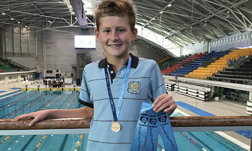 Angus Ciesiolka with his bronze medal and finals ribbons at the NSW Primary Schools Sports Association Swimming Championships at the Sydney Olympic Park Aquatic Centre last week.