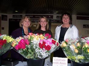 Photo: Alumni Board members Mary Jo, Tina, and Cinda sell roses at graduation