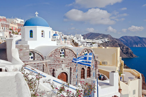 Oia-looking-southa.jpg - A view of a Greek Orthodox church, with a Greek flag fluttering, in Oia on Santorini, Greece.