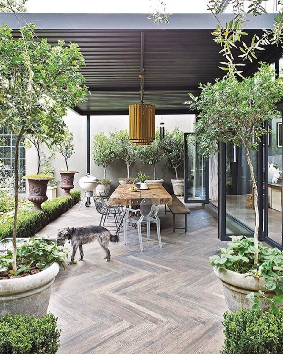 outdoor living area with reclaimed wood table, statement chandelier in gold
