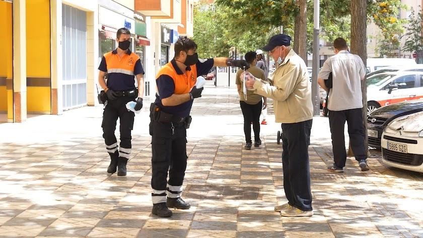 Un miembro de Protección Civil entrega una mascarilla a un transeúnte en la Avenida Rey Juan Carlos.