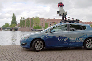 A street view car parked next to an urban waterway