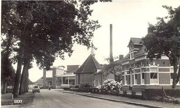 Photo: Kerkstraat rechts de Boerenleenbank. In de tweede woning van rechts was van 1956 tot 1987 het laatste postkantoor gevestigd, waarna het postagentschap werd onder gebracht in de supermarkt. Op de achtergrond de voormalige laatstelijk in 1952 verbouwde zuivelfabriek, die in 1980 wegens opheffing werd afgebroken.