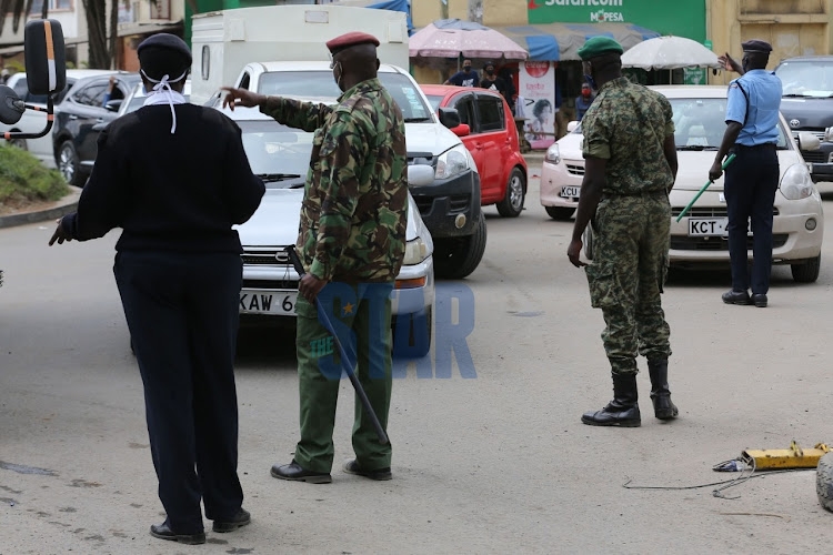 Police officers at General Waruinge Street direct vehicles in Eastleigh Estate in Nairobi on May 21, 2020.