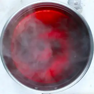 Food coloring, alum powder and water boiling in a pot