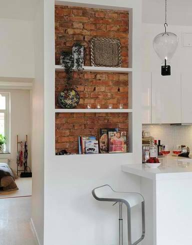 Tijolinho usado como detalhe da decoração, em nicho atrás das prateleiras da cozinha. Uma maneira de contar um pouco da história do imóvel, em equilíbrio com uma decoração mais moderna.