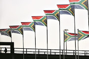 FILE PICTURE: A worker passes hundreds of South African flags lining routes in and out of Johannesburg's OR Tambo International airport.