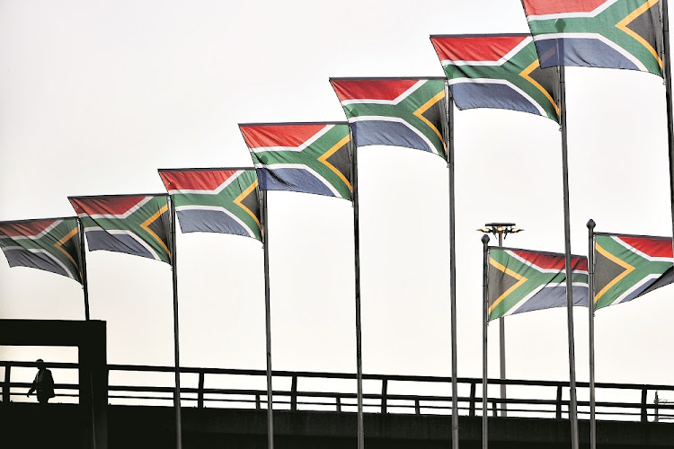 FILE PICTURE: A worker passes hundreds of South African flags lining routes in and out of Johannesburg's OR Tambo International airport