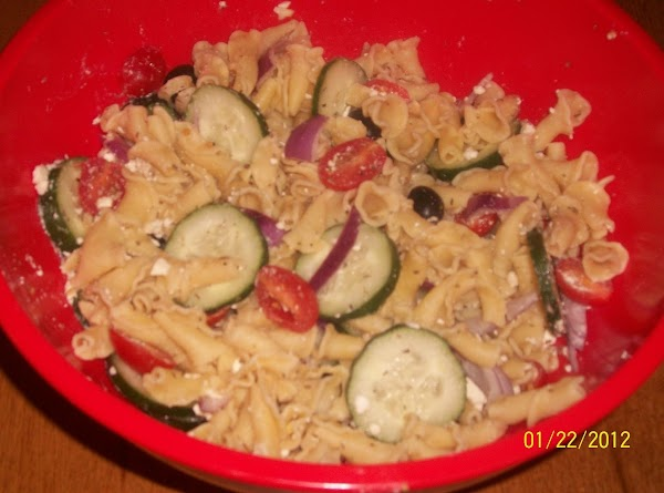 In large bowl, place pasta, cuke, tomatoes, feta, olives, onion, and oregano.  Salt...