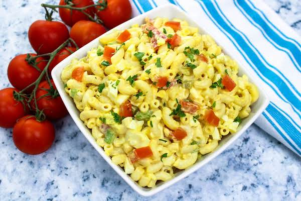 Macaroni Salad With Extra Tomatoes Sprinkled On Top.