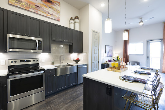 Upscale kitchen and dining area with wood-inspired flooring, white quartz countertops, and stainless steel appliances
