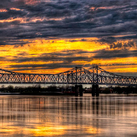 Quiet Time on the Mississippi River by John Larson - Buildings & Architecture Bridges & Suspended Structures ( sky, reflection, barges, sunset, bridge, river, clouds, water )