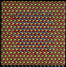 """Photo: """"Hexmatch--detail"""" One of the eighteen tiles, showing a (red, yellow, blue) triplet and a (green, brown, brown) triplet that match from a distance when the eye mixes the colors additively, as predicted from the close proximity of the centroids of the two triplets in L*a*b* color space. A hexagonal grid is chosen to optimally pack circular drops of glaze. To distinguish the dots from the usual pixels found in a rectangular array, I call each dot here a """"trixel"""" and the grouping of three trixels a """"hexel."""" The effective additive hexel color is what is matched in color space."""