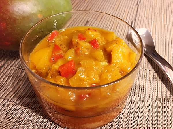 Mango Chutney In A Glass Serving Bowl Sitting On A Beige Table Mat With A Spoon Next To It And A Mango In The Background.