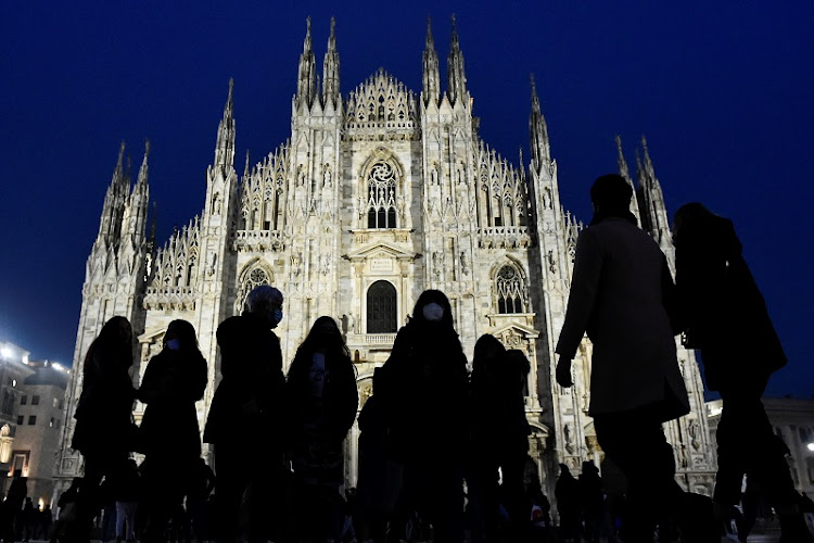 People walk in front the Duomo Cathedral. Italians will only be allowed to leave their homes for work, health or emergency reasons during the Easter holidays.