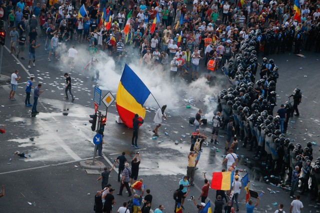 Protesters stand in front of police during a demonstration in Bucharest, Romania, August 10, 2018.