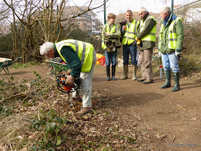Photo: Stuart demonstrates the new auger - making post holes.   Watched by Jasper, Chris, Michael and Rob.