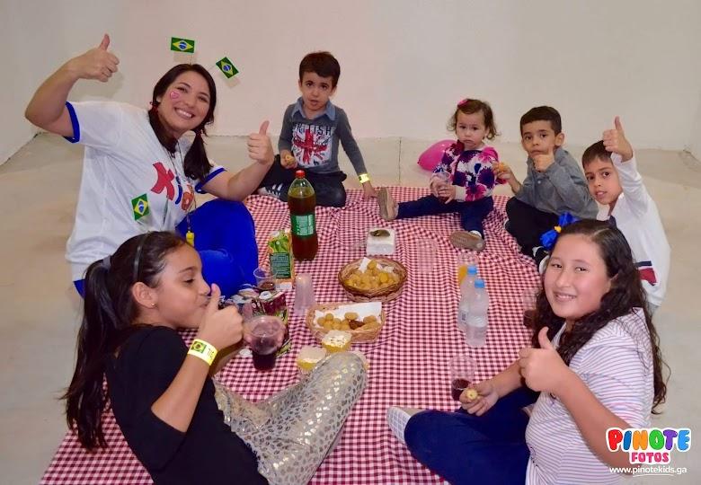 Piquenique sobre uma toalha xadrez e com muitos salgados e doces para as crianças no seu evento infantil em São José dos Campos e Natal. Somos animadores profissionais. Pinote Kids Brasil