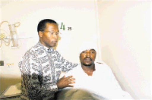LUCKY MAN: IFP member Mduduzi Buthelezi is comforted by Joshua Mazibuko after he was beaten by ANC members. Pic. Mhlaba Memela. © Sowetan.