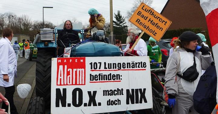 Jecke Umweltschützer mit Schild «Luftkurort Bad Hafen Reisholz», Traktor und Transparent «Hafenalarm. 107 ungenärzte befinden: NOx macht doch nix».