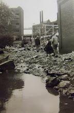Photo: Residents pick their way through debris.
