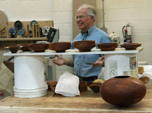 Photo: Demonstrator for the evening, MCW President Phil Brown, discusses design by showing the shapes of a number of bowls.  The influence of Bob Stocksdale on Phil's early work is evident.