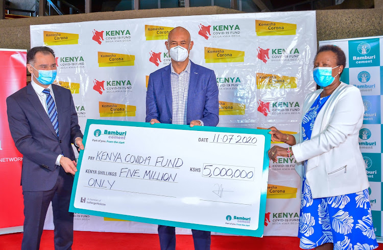 Bamburi Cement Group Managing Director Seddiq Hassani, Covid -19 Emergency Fund , fundraising Chairperson Jermy Awori and the Fund's Chairperson Jane Karuku during the cheque handover ceremony at the Covid -19 Emergency Board offices at KICC./