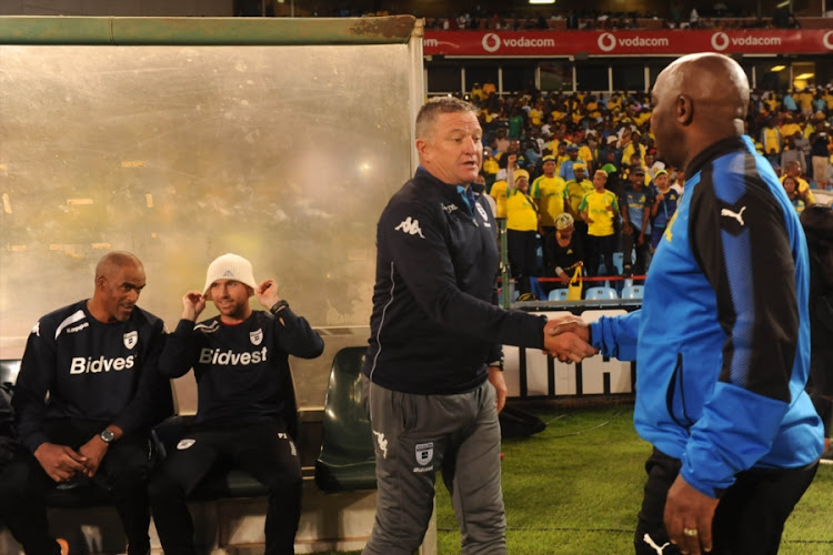 Mamelodi Sundowns' head coach Pitso Mosimane (R) shakes hands with his Bidvest Wits counterpart Gavin Hunt (L) during the Absa Premiership match at Loftus Versfeld Stadium on April 14, 2018 in Pretoria, South Africa.