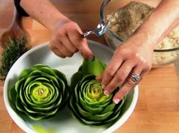 On flat plate that's easy to work on, place one artichoke at a time...