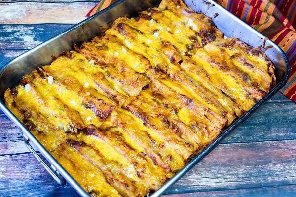 A Tray Of Beef And Cheese Enchiladas.